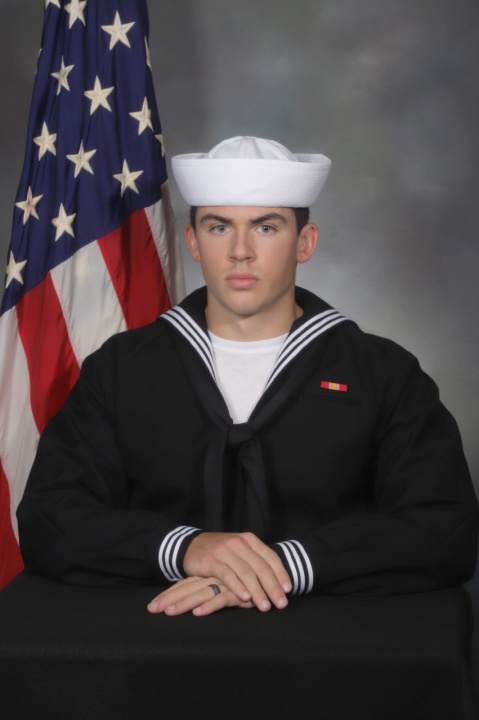 Navy Recruit Dasllin Roberts sits before an American flag.